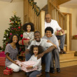 Mixed race family with Christmas tree and gifts — Stock Photo #11882981