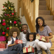 Young African American family with Christmas tree and gifts — Stock Photo