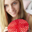Teenage girl holding gift box - Stok fotoğraf