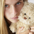 Unhappy teenage girl with cuddly toy - Stock Photo