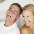 Happy couple sitting back to back on bed — Stock Photo