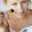 Mid age woman putting on make-up - Stock Photo