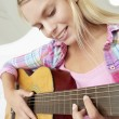 Stock Photo: Teenage girl playing acoustic guitar