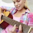 Teenage girl playing acoustic guitar - Stok fotoğraf