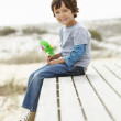 Young boy on beach with windmill — Stock Photo #11883235