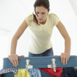 Woman struggling to close suitcase - Stock Photo