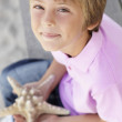 Young boy outdoors holding starfish - Stock Photo