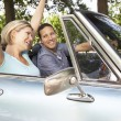 Couple in sports car - Stock Photo