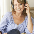 Mid age woman wearing headphones - 图库照片