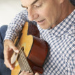 Stock Photo: Mid age mplaying acoustic guitar