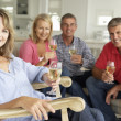 Mid age couples drinking together at home — Stok fotoğraf