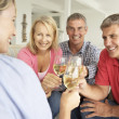 Foto Stock: Mid age couples drinking together at home