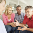 Mid age couples chatting at home - Foto Stock