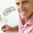 Stock Photo: Mid age mpainting with watercolors