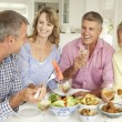 Mid age couples enjoying meal at home - Stok fotoğraf