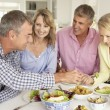 Mid age couples enjoying meal at home - Foto Stock