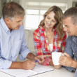 Mid age couple with financial advisor at home — Stock Photo #11883445