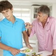 Father making teenage son do housework — Stock Photo #11883481
