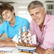 Stock Photo: Father and teenage son model making and painting