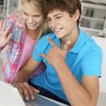 Teenage boy and girl using laptop — Stock Photo #11883494