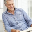 Senior man relaxing at home with a book — Stock Photo #11883633