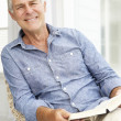 Senior man relaxing at home with a book — Stock Photo #11883634