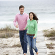 Couple running along beach path — Stock Photo