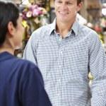 Man serving customer in florist — Stock Photo