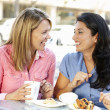 Women chatting over coffee and cakes - 图库照片
