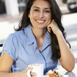 Hispanic woman sitting at sidewalk café — Stock Photo #11884184