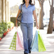 Hispanic woman carrying shopping — Stock Photo