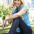 Woman in city park talking on phone — Stock Photo #11884228