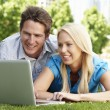 Stock Photo: Couple using laptop in city park