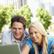 Couple using laptop in city park — Stock Photo