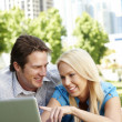 Couple using laptop in city park — Stock Photo #11884246