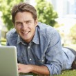 Man using laptop in city park — Stock Photo