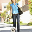 Woman walking with dog in city street — Stock Photo