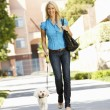 Woman walking with dog in city street — Stock Photo #11884265