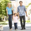 Family walking with dog in city street — Stock fotografie