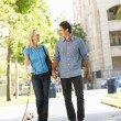 Couple walking with dog in city street — Stock Photo