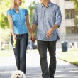 Couple walking with dog in city street — Foto Stock