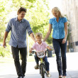 Parents with boy on bike — Stock Photo