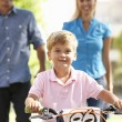 Parents with boy on bike - Stock Photo