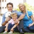 Couple in city park with young son and dog — Stock Photo #11884283