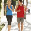 Couple running on city street — Stock Photo