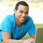 Young man using laptop outdoors — Stock Photo