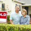 Senior pareja hispana fuera de casa con cartel vendido — Foto de Stock