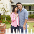 Hispanic couple outside new home - Stock Photo