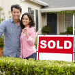 Hispanic couple outside home with sold sign — Foto de stock #11884480