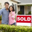 Hispanic couple outside home with sold sign — Stock Photo